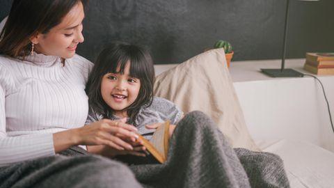 Mutter und Tochter kuscheln auf dem Bett