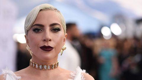Eine weiße, blonde Frau in weißem Abendkleid und mit goldenen Ohrringen schaut ernst in die Kamera