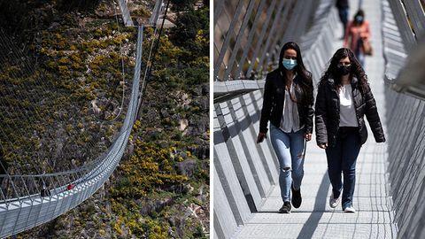 Links spannt sich eine stählerne Hängebrücke über eine bewaldete Schlucht, recht gehen zwei junge Frauen in schwarzen Jacken