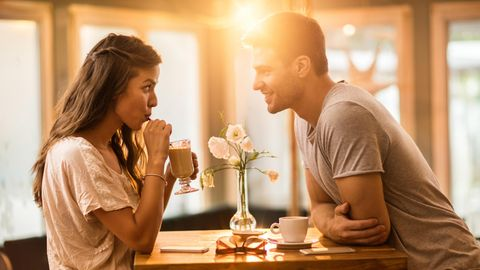 Eine junge Frau und ein junger Mann beim Date im Café. Sie trinkt aus dem Strohhalm, während er sich über den Tisch vorbeugt.