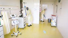 Zwei Frauen reinigen ein Krankenhaus-Zimmer für Covid-Patienten