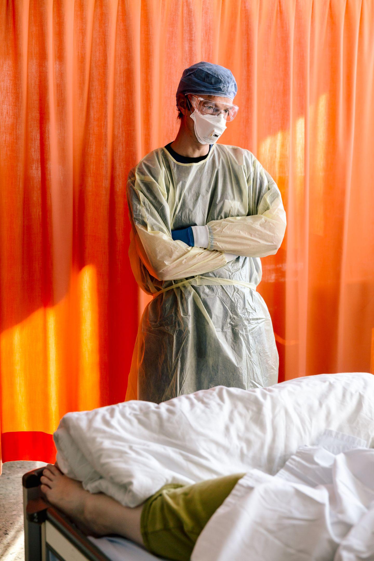 Ein Arzt steht am Bett einer Covid-Patientin mit schwerer Atemnot