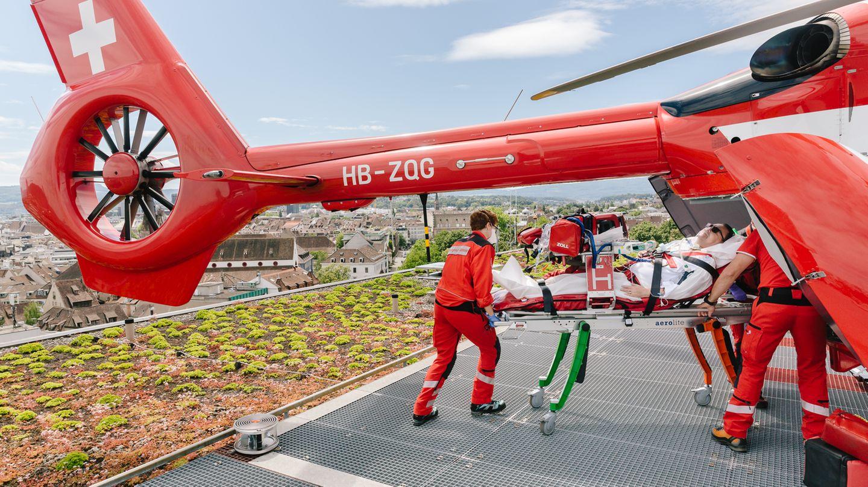 Herr H., ein Schweizer Covid-Patient, wird auf einer Liege in einen Hubschrauber getragen.