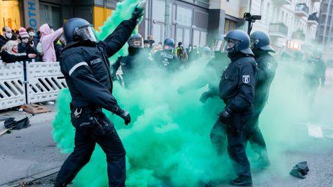 Polizisten versuchen beim Demonstrationszug linker und linksradikaler Gruppen Pyrotechnik zu beseitigen