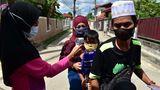 Maung, Thailand. Eine Helferin prüft an einem Checkpoint die Temperatur eines Kindes, das mit seinenEltern auf einem Motorroller unterwegs ist. In dem Land steigen die Infektionszahlen mit dem Coronavirus stark an. Die Regierung hat die Beschränkungen verschärft.