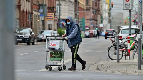 Ein obdachloser Mann schiebt einen Einkaufswagen über eine Straße.