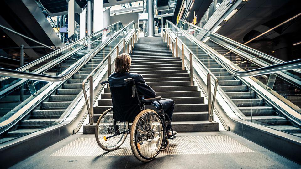 Ein Mann in einem Rollstuhl steht vor einer Treppe
