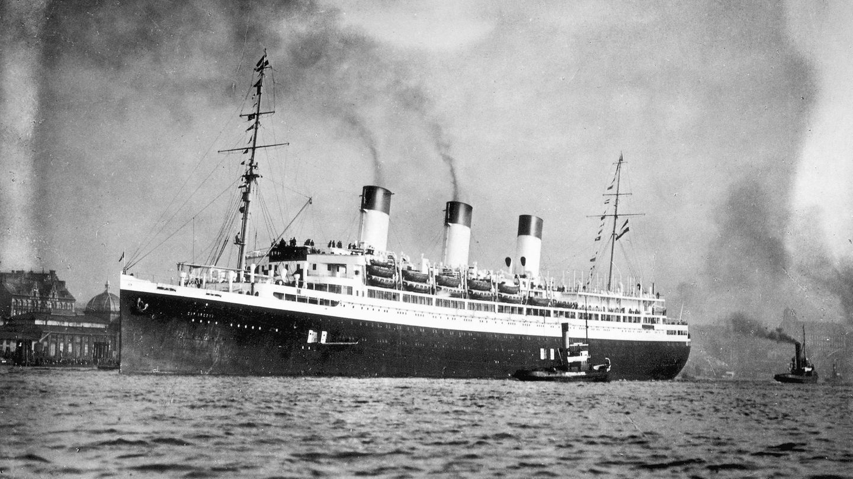 """3.Mai 1945: Die """"Cap Arcona"""" wird bombardiert– und mit ihr Tausende KZ-Häftlinge  Das Ende des Zweiten Weltkrieges war nur noch wenige Tage entfernt, als bei einer Schiffskatastrophe TausendeKZ-Häftlinge in der Ostsee starben. Mehr als 9000 Inhaftierte wurden vor den anrückenden britischen Truppen in die Lübecker Bucht gebracht und dort auf Schiffe verladen - darunter auch auf die """"Cap Arcona"""" (hier auf der Elbe). Die war mit rund 7500 Häftlingen zeitweise komplett überfüllt. Am 3. Mai griff die britische Luftwaffe die Flotte an, die """"Cap Arcona"""" geriet in Brand und kenterte schließlich. Wegen der geringen Wassertiefe versank das Schiff allerdings nicht komplett und lag auf der Seite. Rund 6400 KZ-Häftlinge starben auf der """"Cap Arcona"""" und dem Frachtschiff """"Thielbek"""", nur rund 400 Menschen überlebten."""