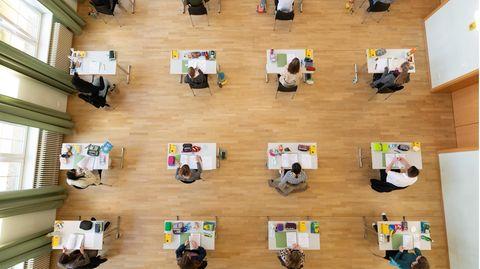 Schüler:innen sitzen während der Abiturprüfung in der Aula