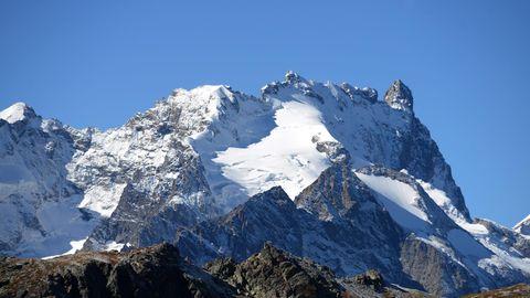 Während im Vordergrund Grün zwischen den Felsen zu sehen ist, bedeckt Schnee den Gipfel im Hintergrund
