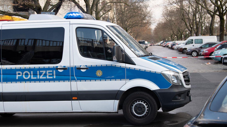 """Ein weißer Transporter mit blauem Streifen und """"Polizei""""-Schriftzug steht quer über die Fahrbahn einer vollgeparkten Straße"""