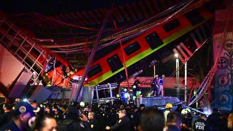 Hinter einer Menschenmenge aus Polizei und Hilfskräften sind die Trümmer zu sehen mit einem rot-grün lackierten U-Bahn-Waggon