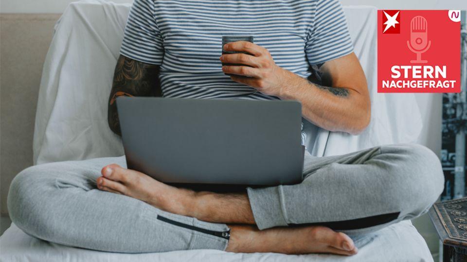 Mann sitzt in Jogginghose und mit Laptop im Bett