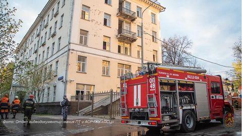 Vor einem hellgelb gestrichenen vierstöckigen Altbau mit Flachdach steht ein rotes Feuerwehrauto mit geöffneten Seitenfächern