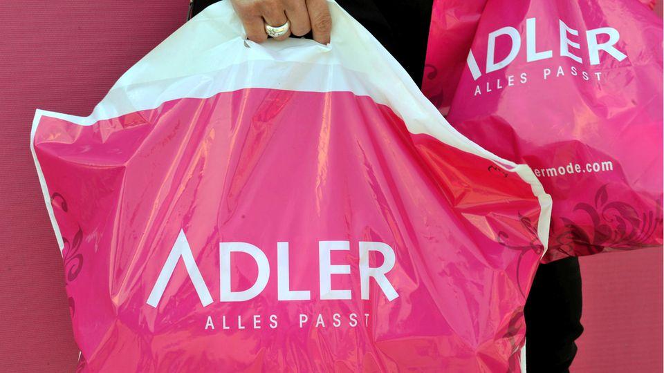 Eine Hand trägt eine Plastiktüte der Textil-Einzelhandelskette Adler Modemärkte