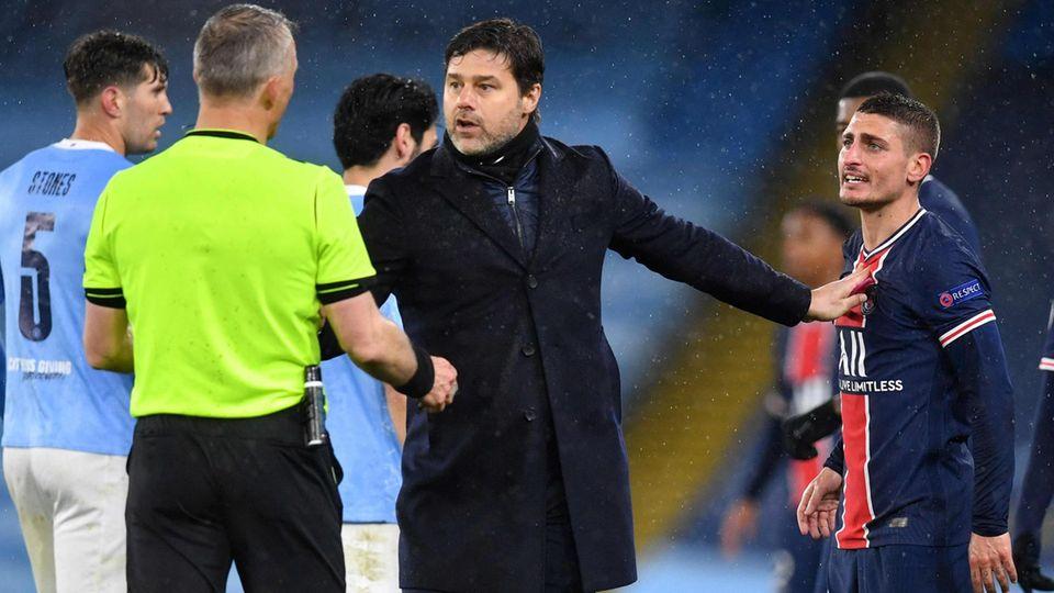 Paris Saint-Germains Trainer Mauricio Pochettino (m.) diskutiert mit dem niederländischen Schiedsrichter Björn Kuipers