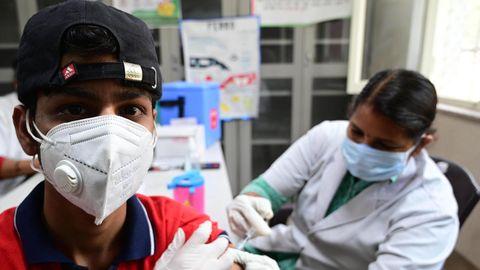 Eine Gesundheitsarbeiterin gibt einem Jungen im indischen Prayagraj die erste Impfdosis