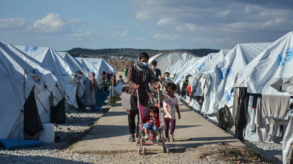 """Eine Frau läuft mit ihren Kindern durch das Lager """"Kara Tepe"""" auf der griechischen Insel Lesbos."""