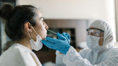Ein Flughafenmitarbeiter testet eine Frau auf Corona