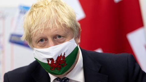 Boris Johnson trägt eine Gesichtsmaske mit der walisischen Flagge