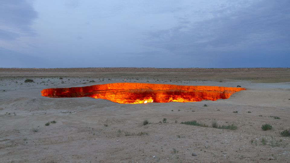 """Bild 1 von 10der Fotostrecke zum Klicken:Der Krater von Derweze in Turkmenistan  Bei einer Bohrung nach Erdgas in der Wüste Karakum stießen die Sowjets 1971 auf Methan, als der Boden bei den Arbeiten plötzlich einbrach und der Krater entstand. Sie entschieden sich für ein Abfackeln des giftigen Gases. Doch bis heute ist die Quelle nicht versiegt. Einheimische sprechen von dem künstlichen Loch als das """"Tor zur Hölle""""."""