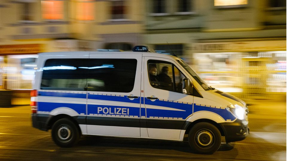 Ein weißer Polizeibus mit blauem Streifen fährt im Dunkeln an erleuchteten Schaufenstern vorbei durch eine menschenleere Straße