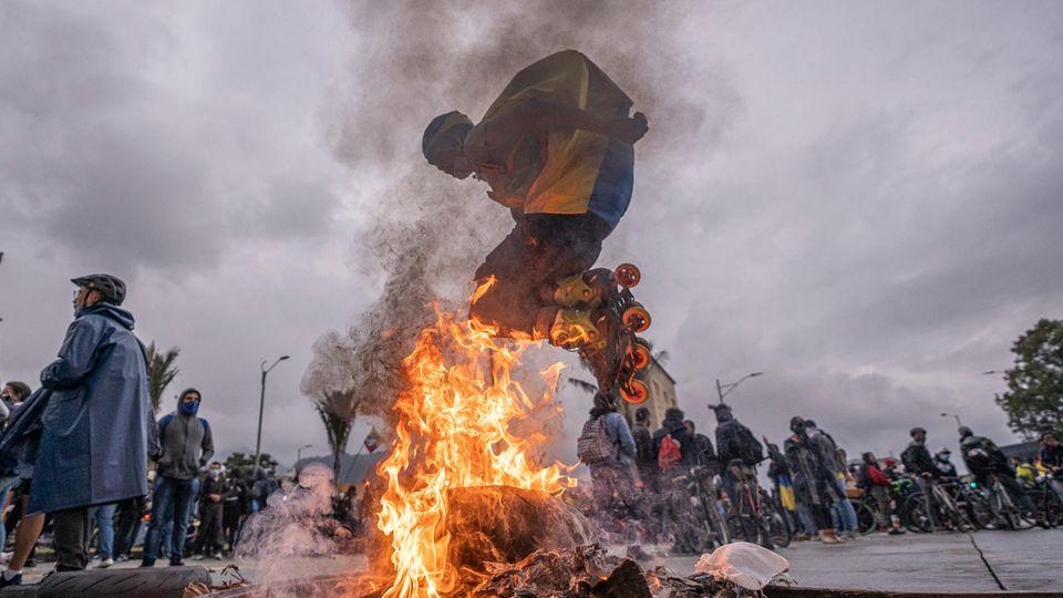 In der kolumbianischen Hauptstadt springt ein Demonstrant in Roller Skates über ein Feuer