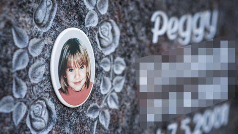 Ein Gedenkstein mit dem Porträt des Mädchens Peggy auf einem Friedhof