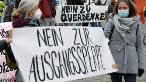 """Demonstranten mit einem Banner mit der Aufschrift """"Nein zur Ausgangssperre"""""""