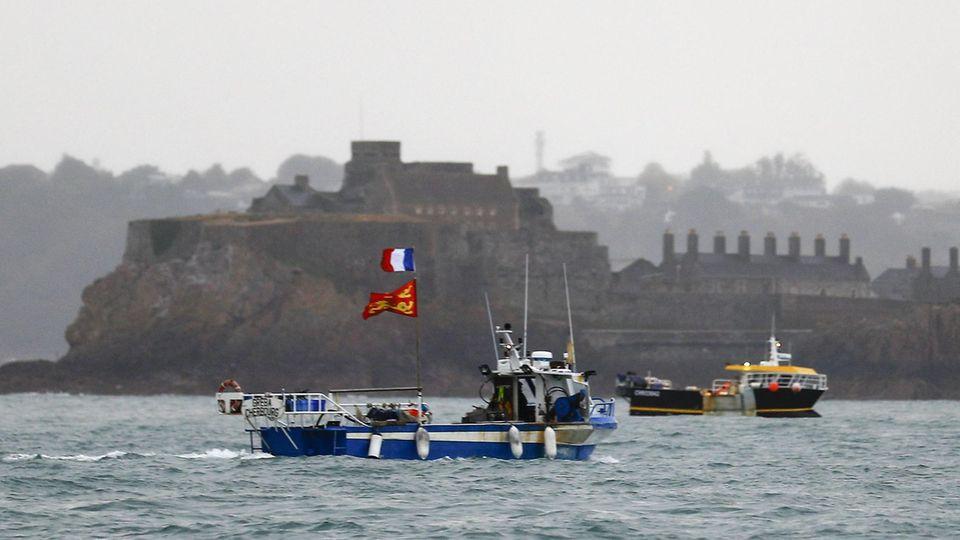 Bei trübem Wetter liegt ein Fischerboot vor der Insel Jersey.