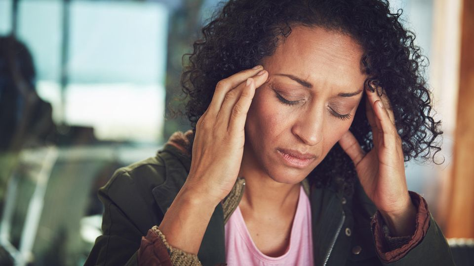 Eine Frau reibt ihre schmerzenden Schläfen.