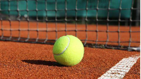 Tennisball liegt vor einem Netz.