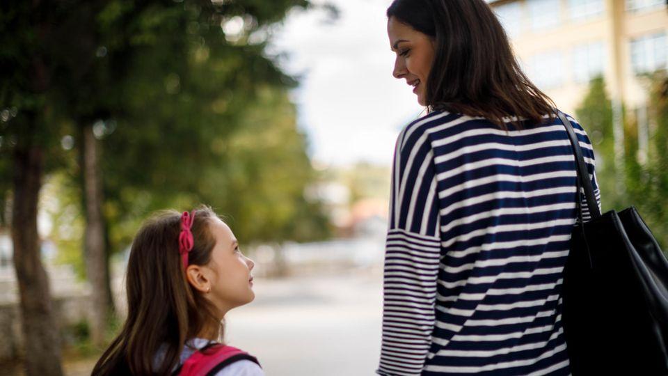 Mutter und Tochter laufen Hand in Hand über eine Straße mit Bäumen