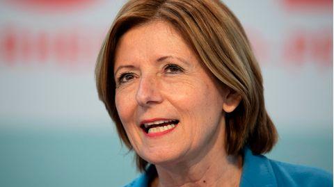 Eine weiße Frau mit schulterlangen, hellbraunen Haaren spricht und lächelt dabei. Sie trägt ein hellblauen Blazer