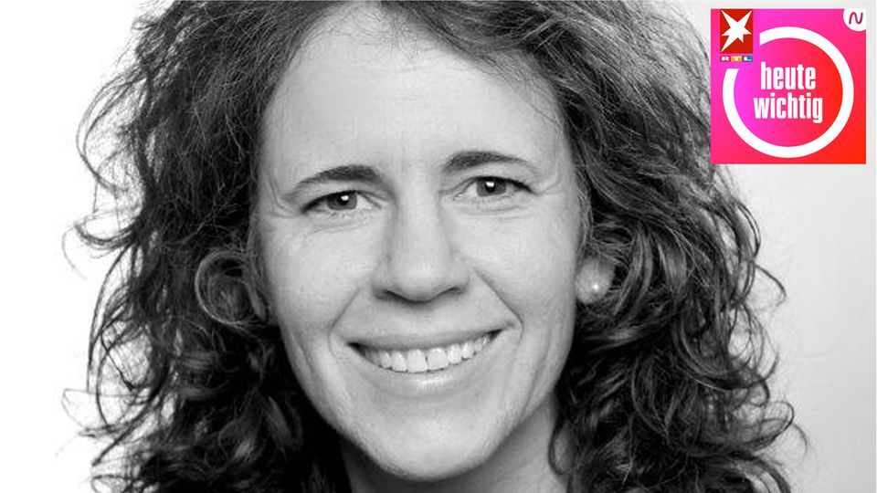 Eine weiße Frau mit langem, gewelltem Haar lächelt auf einem Schwarz-Weiß-Foto