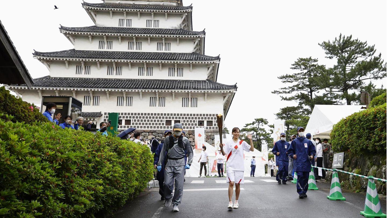 Eine Teilnehmerin des olympischen Fackellaufs läuft am Schloss Shimabara vorbei