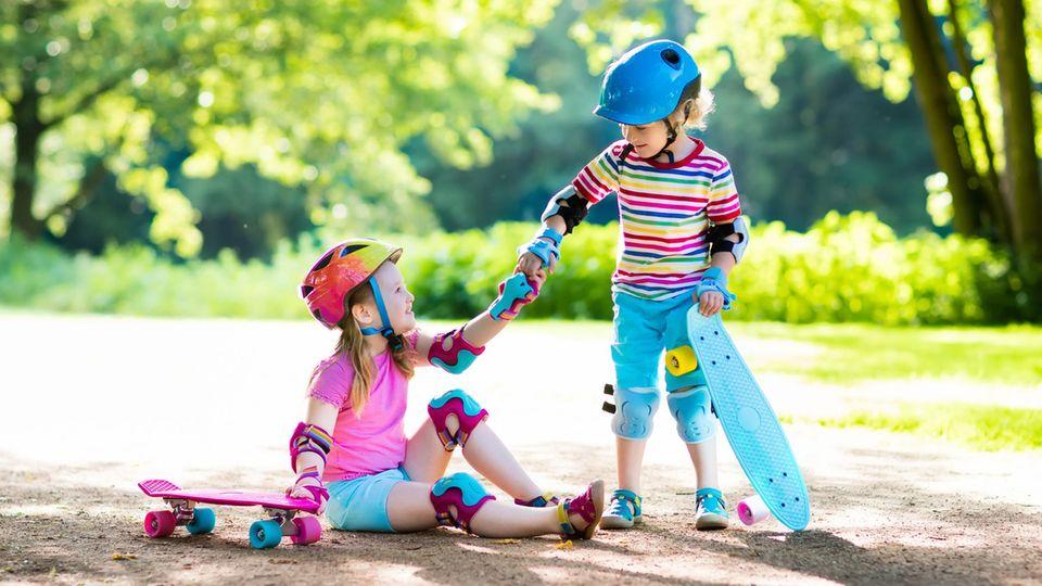 Skateboards für Kinder: Zwei kleine Mädchen sind mit ihren Skateboards in einem Park