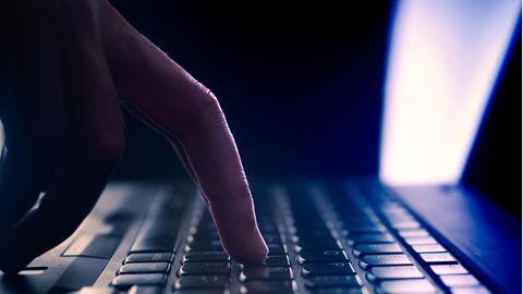 Finger tippt auf eine Tastatur.