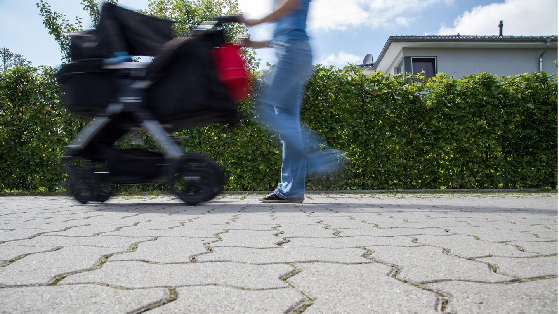 Eine Frau läuft mit Kinderwagen über den Asphalt