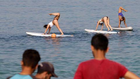Junge Frauen praktizieren Yoga auf Paddle Boards auf dem Wasser