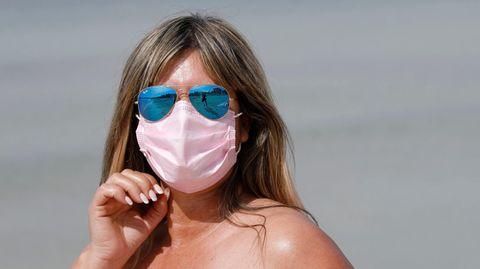 Eine dunkelblonde weiße Frau steht an einem Strand in der Sonne. Sie trägt eine blau verspiegelte Pilotenbrille sowie eine Maske