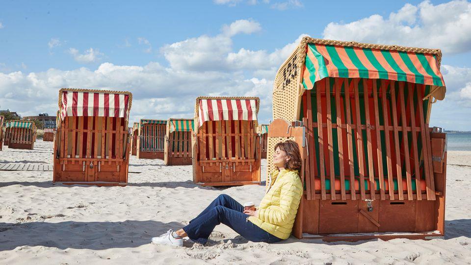 Eine Frau in hellgelber Steppjacke sitzt mit dem Rücken an einen Strandkorb gelehnt an einem Sandstrand und genießt die Sonne