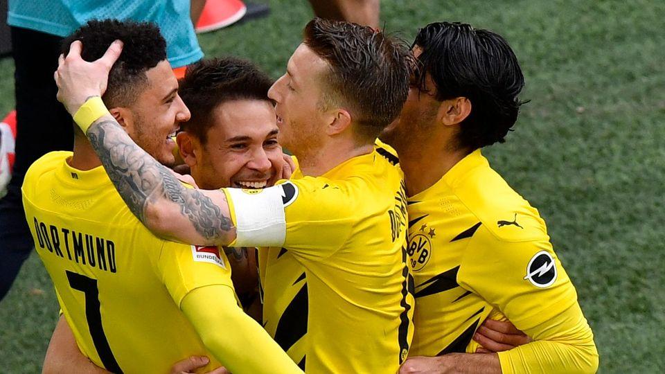 Fußballspieler in schwarz-gelben Trikots jubeln gemeinsam