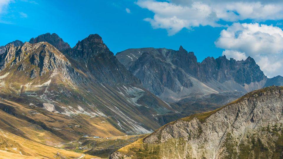Unter leicht bewölktem Himmel ragen hinter einem grünen Tal mehrere Fels-Gipfel in die Höhe