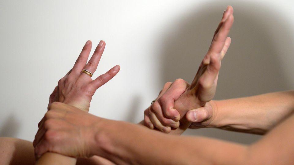 Die Arme eines Mannes (r) halten mit Gewalt die Arme einer Frau fest (gestellte Szene)