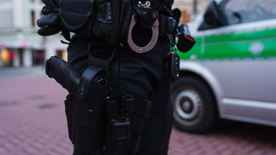 Ein Polizeibeamter steht neben seinem Einsatzfahrzeug