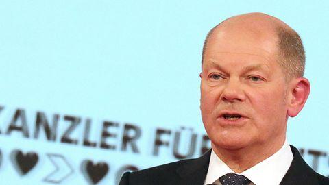 Ein weißer Mann mit kurzrasiertem Haarkranz spricht in Anzug und Krawatte in ein kleines schwarzes Mikrofon