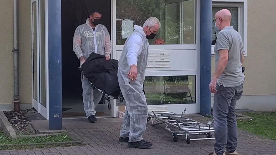 Zwei Männer tragen einen schwarzen Leichensack aus einem gläsernen Hauseingang, vor dem ein dritter Mann mit einer Trage wartet