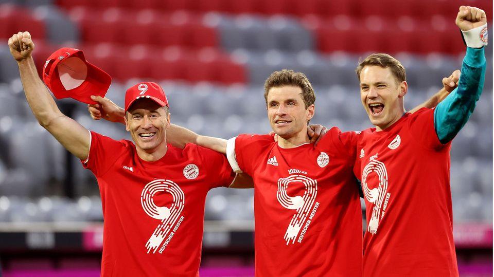 In roten T-Shirts mit einer weißen 9 und dem Wappen des FC Bayern München stehen drei Fußballer Arm in Arm jubelnd im Stadion