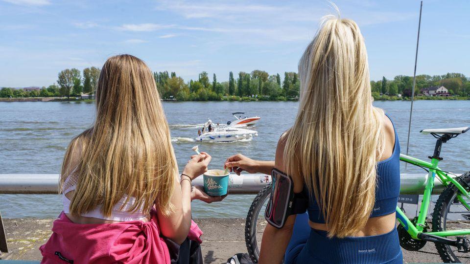 Zwei junge Frauen mit langen, blonden Haaren schauen auf einen Fluss, während sie sich einen Pappbecher Eis teilen